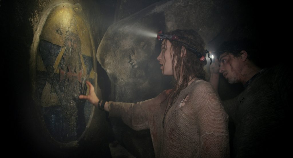 two people exploring the catacombs